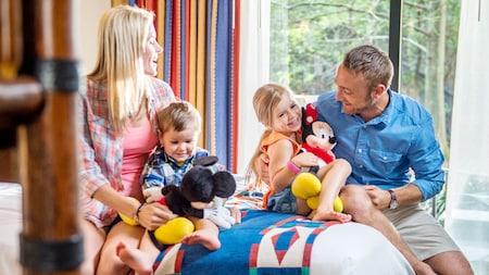 Un padre, una madre, su hijo e hija sonriendo y sentados en una cama en una habitación de hotel