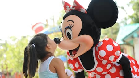 A girl kisses Minnie Mouse's nose