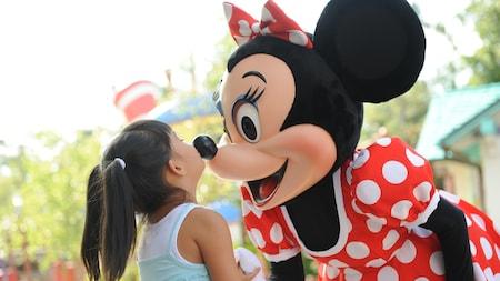 Una niña besa la nariz de Minnie Mouse