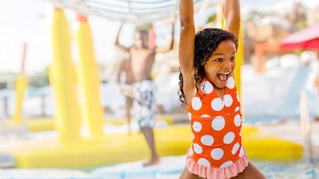 Menina em trajes de banho sorri em um parque aquático