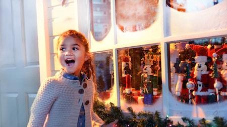 Una niña sonriente está parada cerca de un escaparate navideño decorado con cascanueces en forma de Mickey Mouse