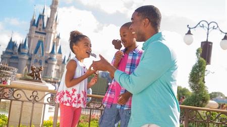 Un papá y sus 2 hijas comen barras de helado en forma de Mickey con el Cinderella Castle de fondo