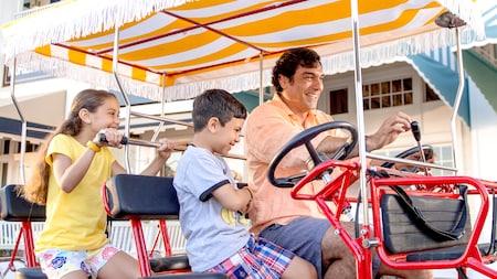 Un papá y 2 hijos andan en una bicicleta surrey por la pasarela del Disney BoardWalk Inn Resort