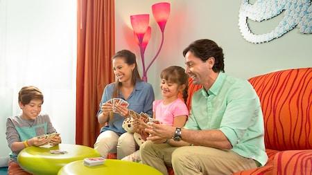 Una familia de 4integrantes juega a las cartas en la habitación temática de Little Mermaid en Disney's Art of Animation Resort