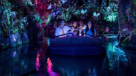 Los Visitantes miran con sorpresa mientras flotan por una selva bioluminiscente a bordo de Na'vi River Journey