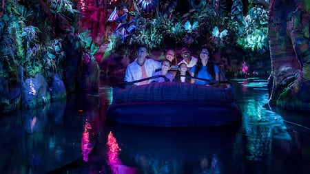 Visitantes admiram encantados enquanto flutuam por uma floresta bioluminescente a bordo da Na'vi River Journey