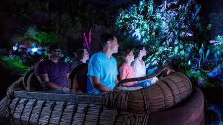Cinco Visitantes navegan en un bote por la atracción Navi River Journey
