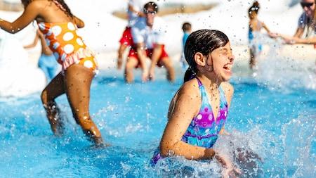Uma garotinha senta em uma piscina rasa e espirra água no Tike's Peak no Disney's Blizzard Beach