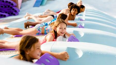 Oito jovens visitantes, deitados em esteiras de tobogã, se preparam para iniciar uma corrida no tobogã aquático