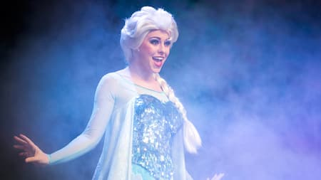 Queen Elsa sings on stage, surrounded by an icy mist