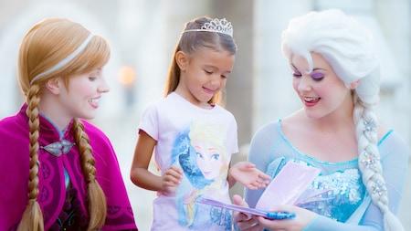 Una pequeña niña con una tiara y una camiseta de Elsa recibe un autógrafo de las verdaderas Anna y Elsa