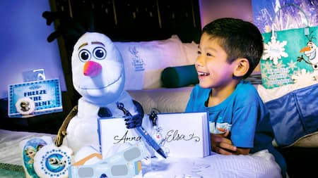 A boy looks at his Frozen gifts, including a plush Olaf and an autograph book signed by Anna and Elsa