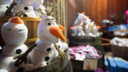 A barrel in a retail store filled with Olaf plush from Disney's animated film Frozen