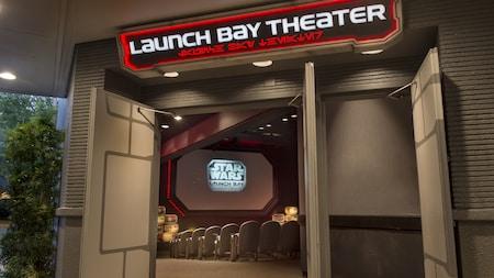 """Una pantalla con un logotipo que que lee """"Star Wars Launch Bay"""" y algunos de los asientos del teatro están enmarcados por puertas abiertas sobre las cuales un signo con las palabras """"Launch Bay Theater"""" en letras con la forma de personajes que recuerdan un alfabeto alienígena"""