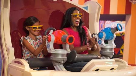 Uma garota e uma mulher usam óculos especiais para visualizar a atração, sentadas em um Carnival Ride Tram