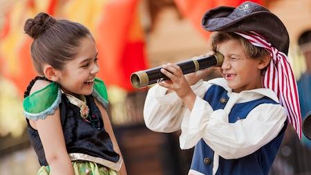Menina vestida como Anna de Frozen ri, enquanto o irmão vestido de pirata espia por uma luneta
