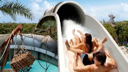 Una pareja comparte un recorrido en balsa recostados hacia atrás mientras descienden por la montaña rusa acuática Crush 'n' Gusher