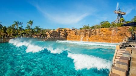 Las olas rompen en Disney's Typhoon Lagoon Surf Pool con el Mount Mayday detrás