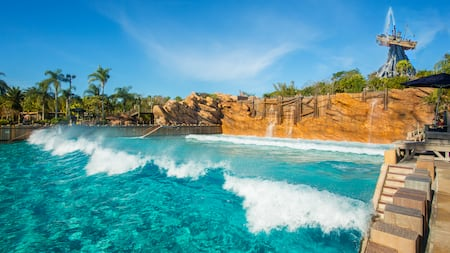 Waves break in Disney's Typhoon Lagoon Surf Pool with Mount Mayday beyond