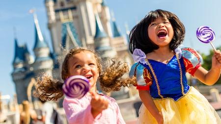Two little girls wearing princess costumes near Cinderella Castle