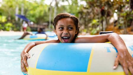A young girl floating in an inflatable tube in a swimming pool
