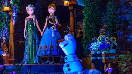 Anna e Elsa de mãos dadas, com Olaf por perto