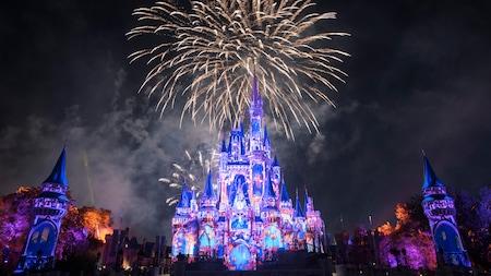 Imagens são projetadas no Cinderella Castle enquanto fogos de artifício explodem no céu
