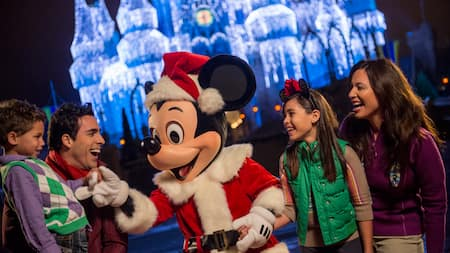 Papai Noel Mickey de mãos dadas com uma família vestida para a estação com luzes brilhando no Castelo da Cinderela