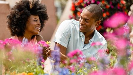 A man hands a flower to a woman