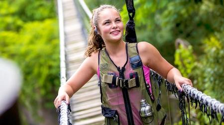 Una huésped cruza un puente de soga durante el Wild Africa Trek en el Parque Temático Disney's Animal Kingdom
