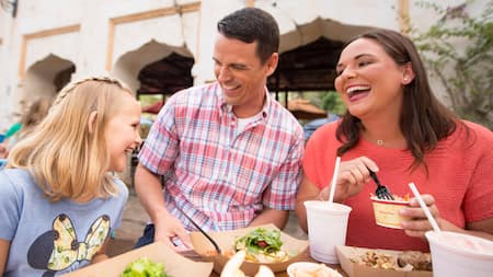 A happy family laughing while they indulge in a dining experience at the Morocco Pavilion in Epcot