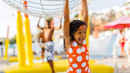 A young girl in a swimsuit smiles in a water park