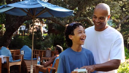 A father and son laugh together as they view a photograph on a camera in front of a shade umbrella and grouping of chairs