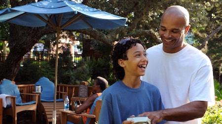 Un padre y su hijo sonríen juntos mientras miran una fotografía en una cámara frente a la sombra de una sombrilla y un grupo de sillas