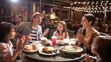 Una familia de 5 brinda durante un almuerzo de celebración, en Disney Springs