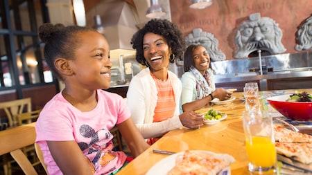 A happy family indulging in pizza and other Italian-style fare at Via Napoli Ristorante e Pizzeria