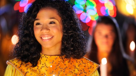 A smiling girl takes part in a holiday candlelight processional