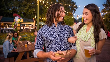 Un couple marche bras dessus bras dessous en savourant des mets au Epcot International Flower & Garden festival