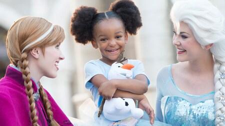 Una Visitante sonríe mientras abraza un peluche de Olaf en un encuentro con Personajes, con Anna y Elsa