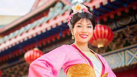 Mulan porte une robe chinoise colorée et des fleurs dans ses cheveux et sourit près du pavillon de la Chine à Epcot