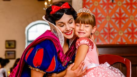 Snow White hugs a little girl wearing a princess dress and crown who sits beside her