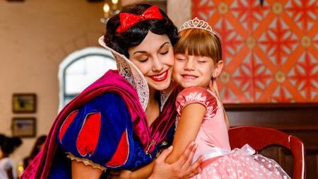 Blanche Neige fait un câlin à une petite fille portant une robe de princesse et une couronne qui est assise à côté d'elle