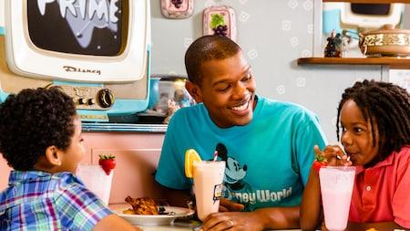 Um pai e seus filhos pequenos sorriem saboreando milk-shakes gelados em uma cabine do 50's Prime Time Café