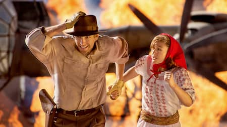 Indiana Jones and Marion running from a fiery aircraft during Indiana Jones Epic Stunt Spectacular!