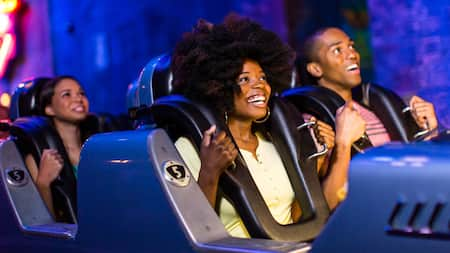 A group of Guests smiles in anticipation prior to launch on Rock 'n' Roller Coaster Starring Aerosmith
