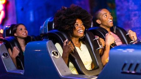 Un groupe de visiteurs sourient en attendant le lancement de Rock 'n' Roller Coaster Starring Aerosmith