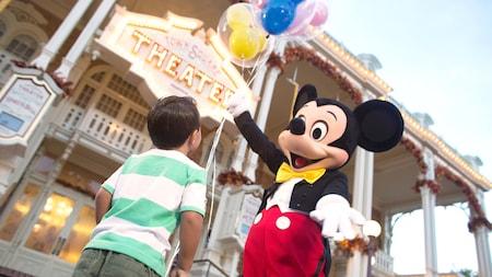 Mickey Mouse ofreciendo un manojo de globos a un joven Visitante en el Parque Temático Magic Kingdom