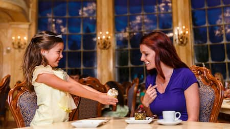A young female Guest in a tiara holds a cupcake during a dining experience at Be Our Guest Restaurant