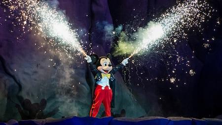Mickey extiende los brazos y sonríe mientras miles de destellos luminosos salen volando de la punta de los dedos