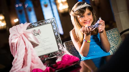 A little girl wearing a tiara sits next to a framed royal proclamation and holds a glass slipper